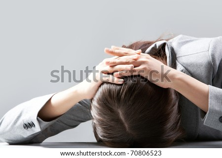 A young woman hiding her face on table - stock photo