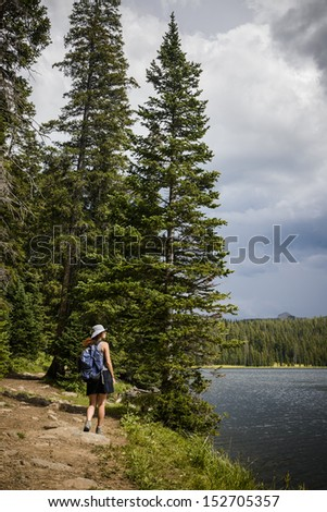 a young woman hiking next to a lake in the mountains - stock photo