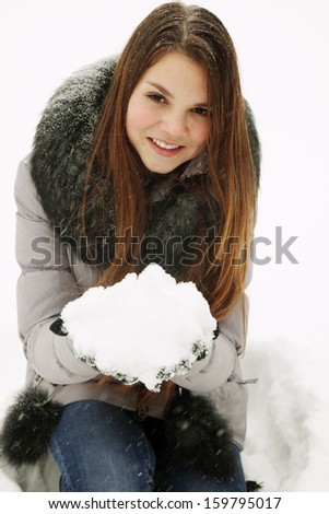 A young woman holding a bunch of snow - stock photo