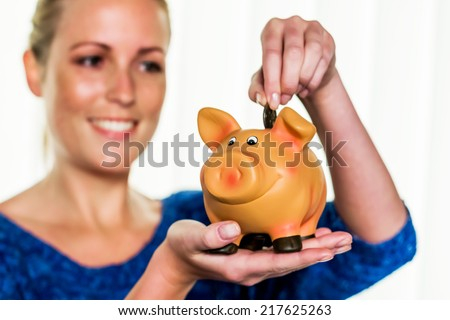 a young woman holding a piggy bank in her hand. , create photo icon for save money and retirement. - stock photo