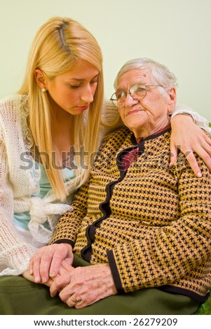 A young woman holding an older one whit love and empathy - part of a series. - stock photo