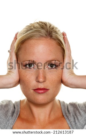 a young woman holding her ears. symbol photo for do not want to hear disputes and conflicts, as well as loud undtinnitus - stock photo