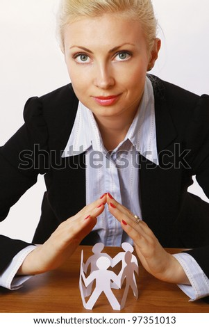 A young woman holding paper people sitting at the desk. - stock photo