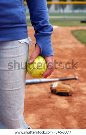 A young woman holds a softball.  Mitt and bat are out of focus on the infield. - stock photo