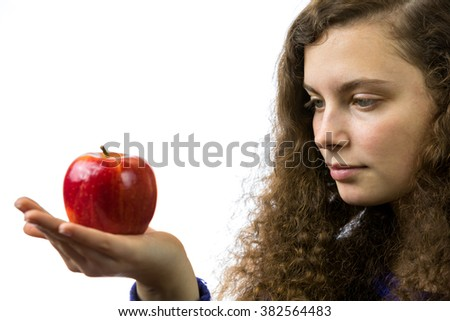 A young woman holds an apple in her hand and smiles - stock photo