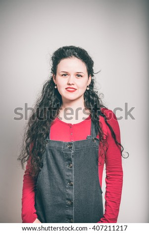 A young woman holds hands in pockets, wearing a overalls, close-up isolated on a gray background - stock photo