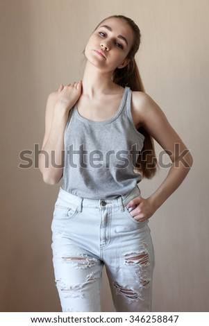 A young woman in a gray T-shirt and torn jeans - stock photo