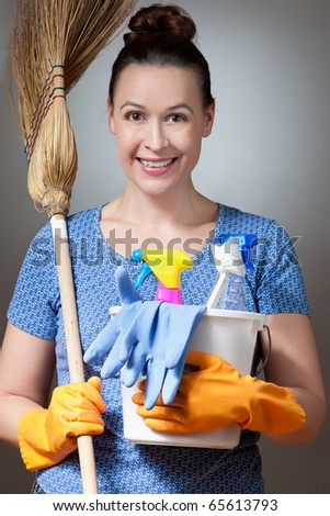 A young woman in a housewife role ready for cleaning. - stock photo