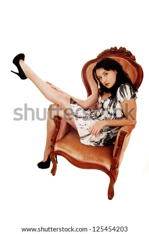 A young woman in an black and white dress and high heels sitting on an pink armchair with her finger in her mouths, for white background. - stock photo