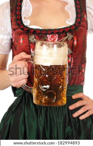 A young woman in Bavarian Dirndl is holding a stein with one liter beer - stock photo