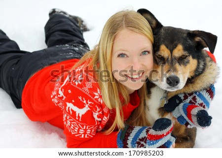 a young woman in her thirties is laying outside in the winter snow with her German Shepherd mix dog, hugging him. - stock photo