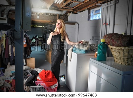 A young woman in in the basement doing laundry and chores while pretending to be in a stage play and acting with a spotlight on her. Use it for an art or - stock photo