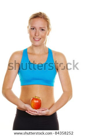 A young woman in sports clothing holding an apple in his hand - stock photo