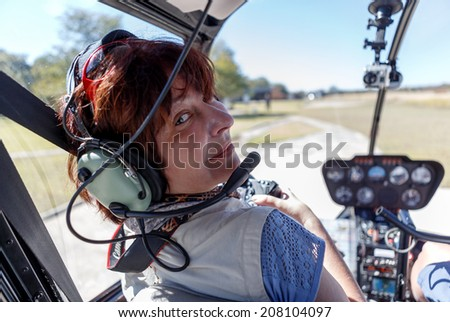 A young woman in the cabin of the helicopter before flying above the Victoria Falls, Zambia - stock photo