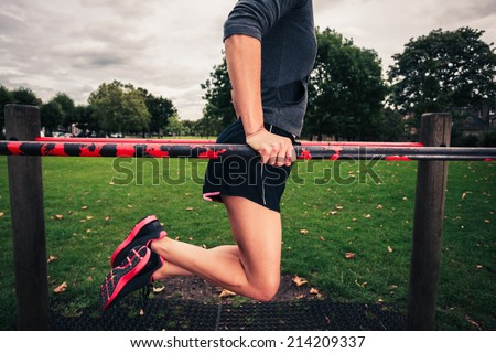A young woman is doing dips on equipment in the park - stock photo