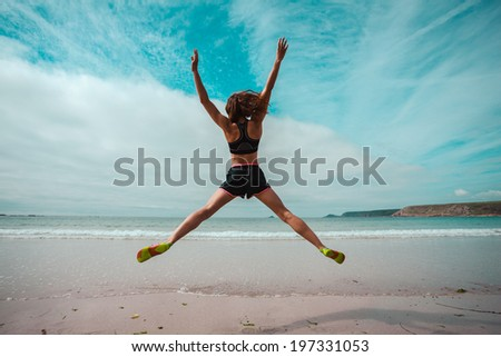 A young woman is doing star jumps on the beach by the sea - stock photo