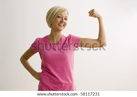 A young woman is flexing her bicep and smiling at the camera.  Horizontal shot. - stock photo