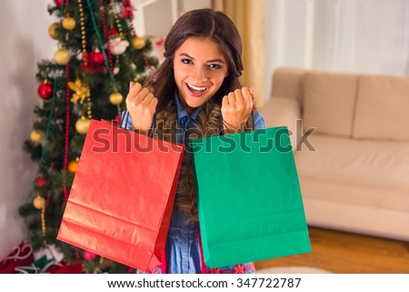 A young woman is happy while celebrating Christmas at home - stock photo
