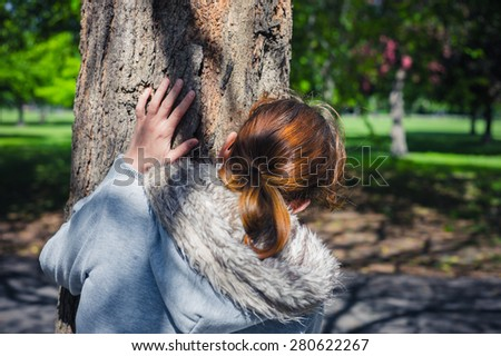 A young woman is hiding behind a tree in the park - stock photo