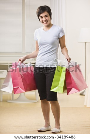 A young woman is holding multiple shopping bags and smiling at the camera.  Vertically framed shot. - stock photo