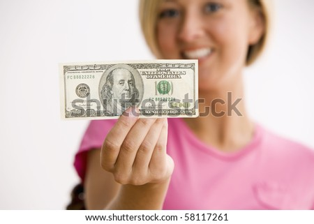 A young woman is holding out a $100.00 bill and smiling at the camera.  Horizontal shot. - stock photo