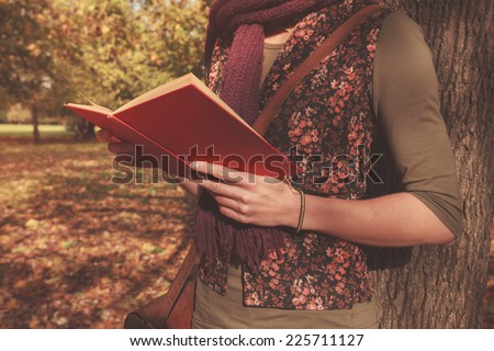 A young woman is leaning against a tree in the park and is reading a book on a sunny autumn day - stock photo