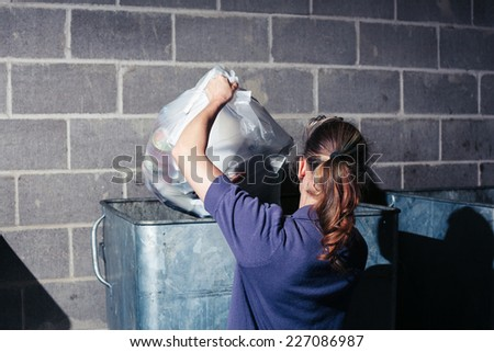 A young woman is putting a bag of rubbish in a large bin at night - stock photo