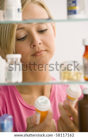 A young woman is reading the labels of to medicine containers from her medicine cabinet.  Vertical shot. - stock photo