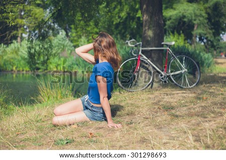 A young woman is relaxing by the water in a park on a summer day  with her bicycle resting against a tree in the background - stock photo