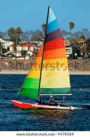 A young woman is sailing in Mission Bay, San Diego. A colorful yacht with rainbow-colored sail stands out against a background of out-of-focus suburban houses... - stock photo