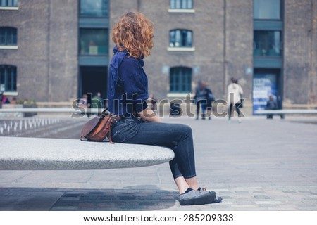A young woman is sitting and relaxing on a granite bench in the city - stock photo