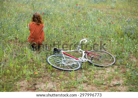 A young woman is sitting in a meadow with a bicycle on the ground next to her - stock photo