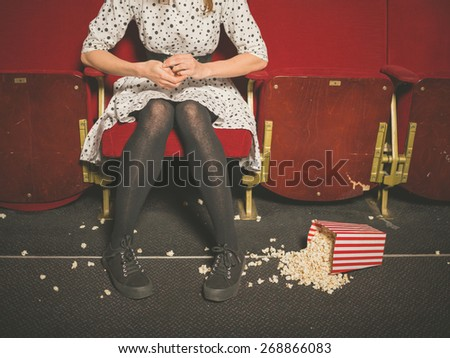 A young woman is sitting in a movie theater with a bucket of popcorn spilled on the floor in front of her - stock photo