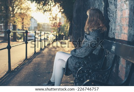 A young woman is sitting on a bench at sunset on an autumn day in the city - stock photo