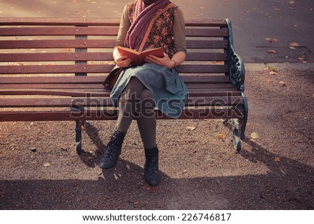 A young woman is sitting on a park bench in the autumn and is reading a book - stock photo