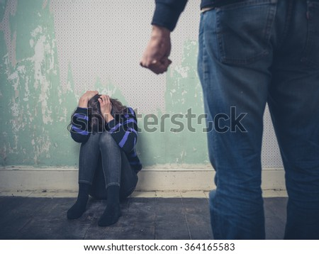 A young woman is sitting on the floor as her partner attacks her - stock photo