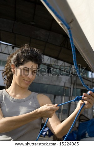 A young woman is smiling as she ties a knot in a rope.  Vertically framed shot. - stock photo