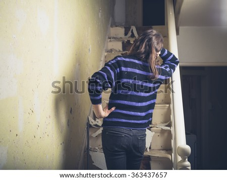 A young woman is standing by a staircase she is renovating - stock photo