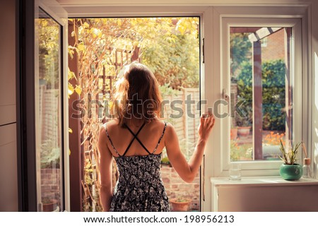 A young woman is standing in the doorway of her kitchen and is looking at the garden at sunrise - stock photo