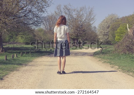 A young woman is standing on a dirt road in a forest - stock photo