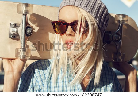 A young woman is standing on the street holding skateboard behind her head. The girl in joyful feelings. Outdoors, lifestyle. - stock photo