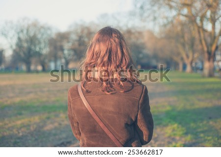 A young woman is walking in the park on a winter's day - stock photo