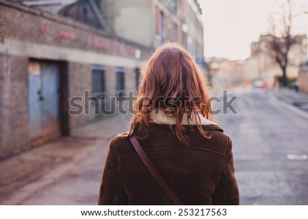 A young woman is walking on the quiet streets of a city in the winter - stock photo