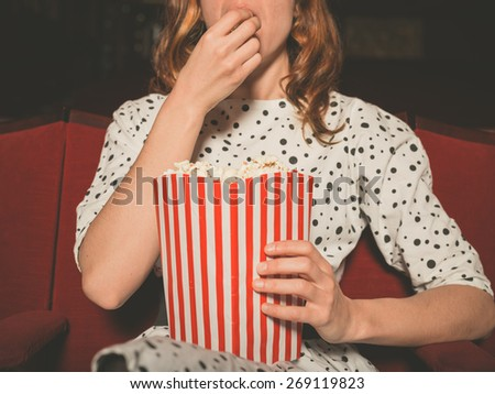A young woman is watching a movie and is eating popcorn at the cinema - stock photo