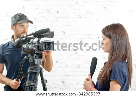 a young woman journalist with a microphone and a cameraman - stock photo