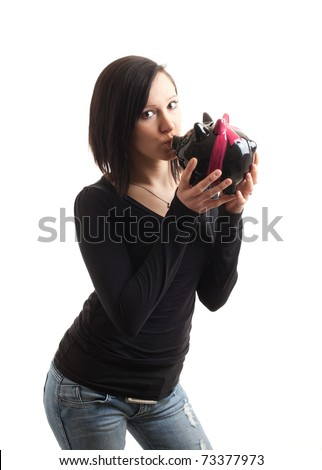 a young woman kissing a piggy bank isolated on white - stock photo