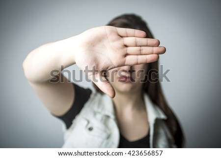 A Young woman laughing, eyes closed and hand showing stop.  - stock photo