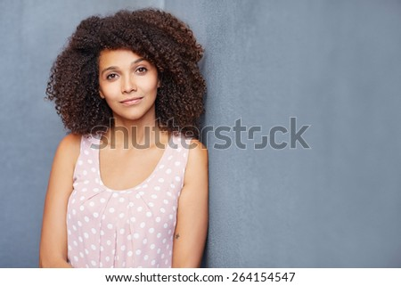 A young woman leaning against a gray wall looking at camera - stock photo