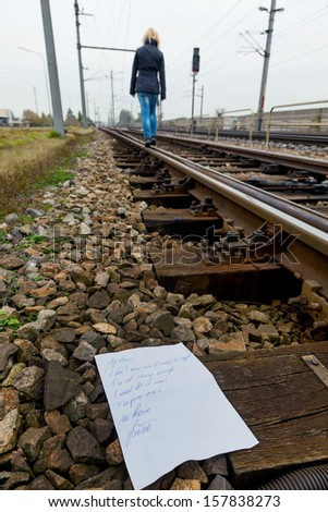 a young woman leaves a farewell letter and goes to commit suicide on a railway. letter in english - stock photo