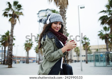 A young woman listening to music on her headphones walking outdoors - stock photo